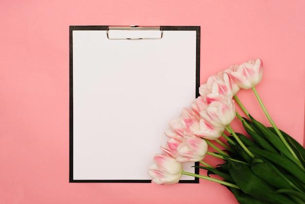 Um lindo buquê de delicadas tulipas rosa repousa sobre um fundo rosa com um lugar para o seu texto