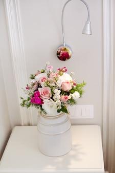 Um lindo buquê de flores delicadas fica na mesa de cabeceira no quarto