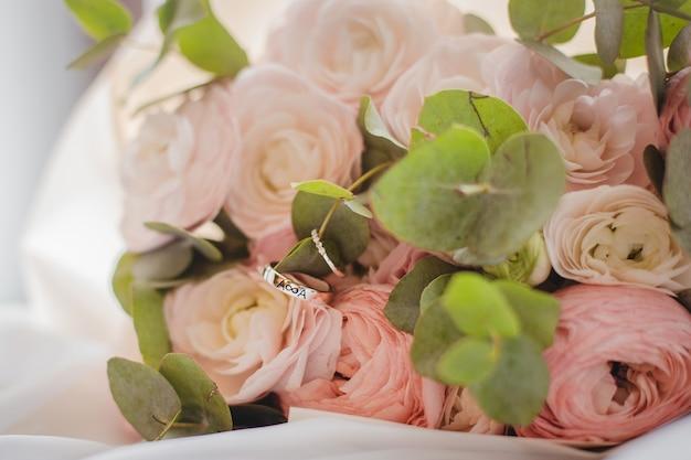 Um lindo buquê de noiva com anéis de casamento. conceito de casamento