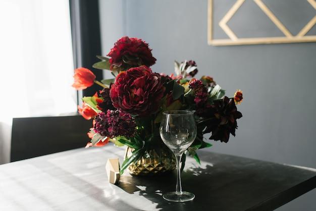 Um lindo buquê de peônias da borgonha em um vaso em cima da mesa na sala de estar com paredes pretas e um copo em cima da mesa