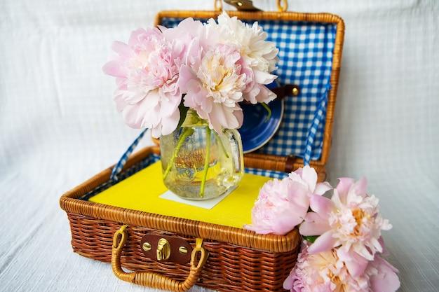 Um lindo buquê de peônias rosa fica em um vaso em uma mala de madeira.