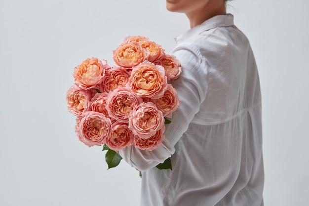Um lindo buquê de rosas cor de rosa é segurado por uma mulher. o melhor presente para uma menina no dia dos namorados.