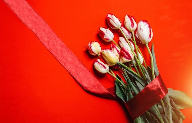 Um lindo buquê de tulipas vermelhas sobre um fundo vermelho