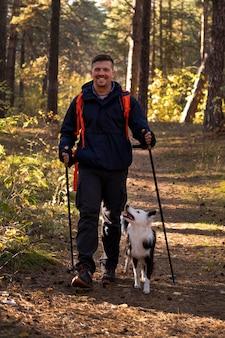 Um lindo cachorro preto e branco e um homem caminhando
