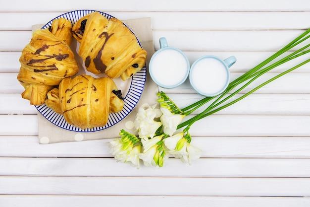 Um lindo café da manhã - croissants em um prato e duas xícaras de cappuccino, um buquê de frésias