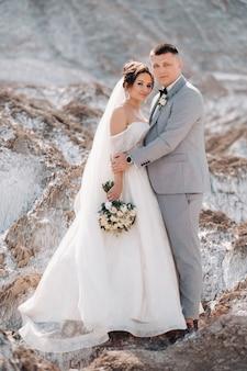 Um lindo casal de amantes posando em uma montanha de sal branco. uma jovem mulher em um vestido de noiva elegante e um homem lindo e elegante em um terno cinza. o conceito do dia do casamento.