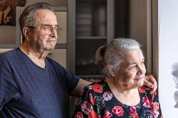 Um lindo casal de idosos está de pé na janela e olha para alguém que está esperando.