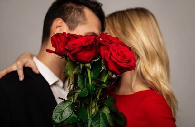 Um lindo casal em trajes elegantes está se escondendo atrás de um lindo buquê de rosas vermelhas enquanto se beijam e se abraçam.