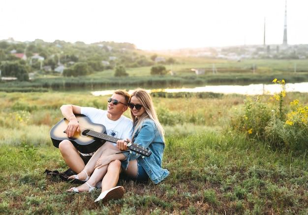 Um lindo casal feliz, apaixonado por óculos de sol, tocando violão e regozijando-se ao pôr do sol