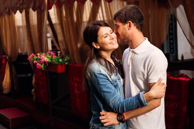 Um lindo casal jovem se abraçando na entrada do café