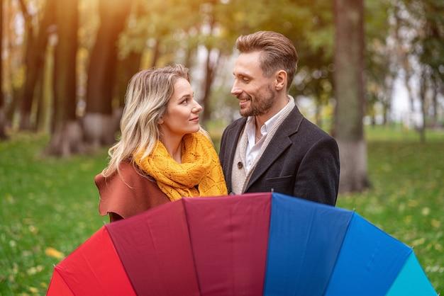 Um lindo casal no parque de outono em tempo chuvoso