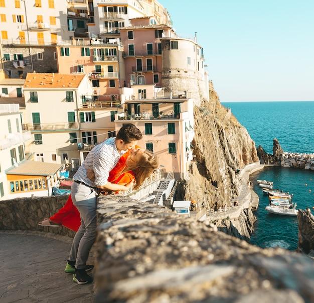 Um lindo casal olhando para o mar em um dia ensolarado e abraçando e beijando