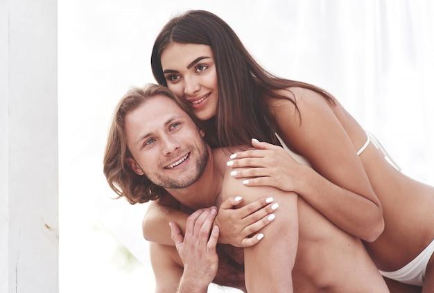 Um lindo casal relaxando na praia, vestindo roupas de banho. atmosfera romântica