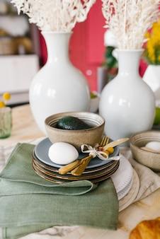 Um lindo cenário de mesa com louças para a celebração da páscoa. ovo no prato