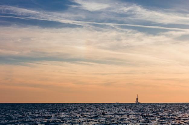 Um lindo céu com um barco no mar com nuvens