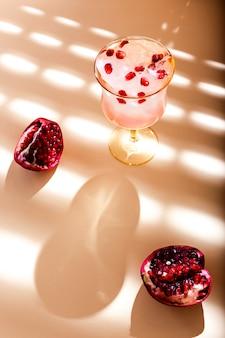 Um lindo copo de água tônica gelada com romã, luz de fundo, sombras agradáveis e reflexos na superfície