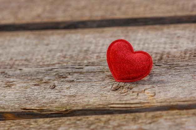 Um lindo coração vermelho encontra-se em um fundo de madeira