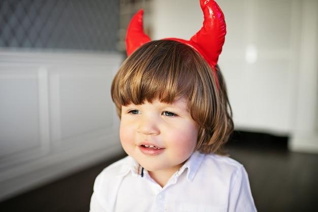 Um lindo garotinho em uma camisa branca com chifres vermelhos ri