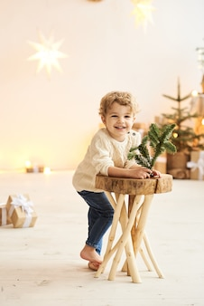 Um lindo garotinho encaracolado encostado em uma cadeira de madeira perto de uma árvore de natal em um quarto branco