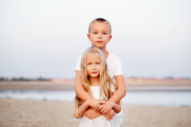 Um lindo irmão mais novo em uma camiseta branca abraça sua irmã mais nova loira