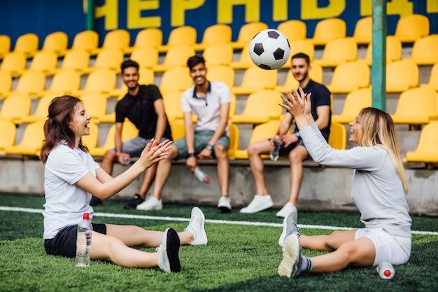 Um lindo jogador de futebol americano alongando os músculos da perna se preparando para a partida no estádio