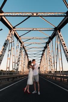 Um lindo jovem casal apaixonado, um homem e uma mulher, se abraçam e se beijam em uma grande ponte de metal ao pôr do sol.