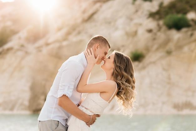 Um lindo jovem casal apaixonado, um homem e uma mulher se abraçam, se beijam perto de um lago azul e areia ao pôr do sol. férias no mar na praia