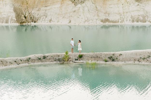 Um lindo jovem casal apaixonado, um homem e uma mulher se abraçam, se beijam perto de um lago azul e areia ao pôr do sol.