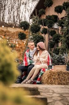 Um lindo jovem casal com roupas brancas está sentado perto de uma árvore de natal no jardim. homem e mulher felizes, romance, celebração de natal, diversão, amor.