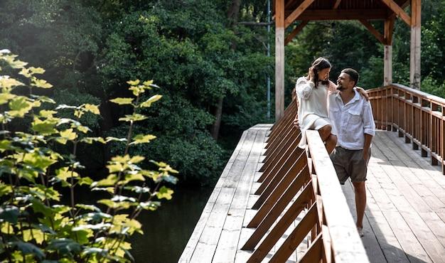 Um lindo jovem casal se comunica em uma ponte na floresta, um encontro na natureza, uma história de amor.