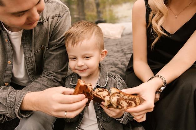Um lindo jovem homem de família e um filho relaxam na floresta na natureza em uma grande tenda redonda com uma cama e um fogão para cozinhar, fazer um piquenique, acampar
