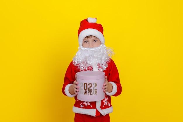 Um lindo menino com roupas de papai noel e uma barba branca artificial segura uma caixa de presente redonda rosa