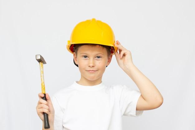 Um lindo menino com um capacete, nas mãos de uma criança com um martelo. o conceito da importância do uso de equipamentos de proteção individual e ferramentas especiais
