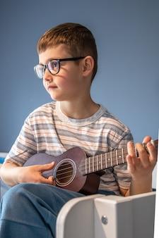 Um lindo menino de óculos aprende a tocar violão ukulele em casa, em seu quarto.