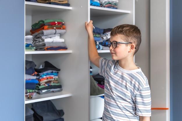 Um lindo menino de óculos fica perto de um guarda-roupa e pensa no que vestir.