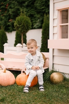 Um lindo menino de quatro anos com roupas brancas brinca do lado de fora perto de uma casa de madeira branca com abóboras