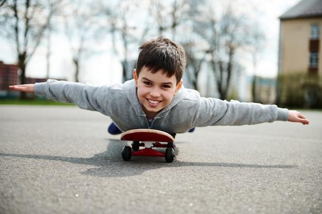 Um lindo menino deitado de barriga no skate com os braços estendidos como asas e imaginando um vôo em um avião