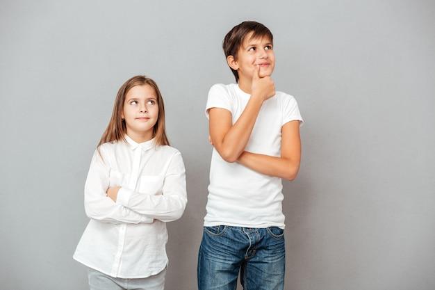 Um lindo menino e uma menina pensativos em pé e pensando