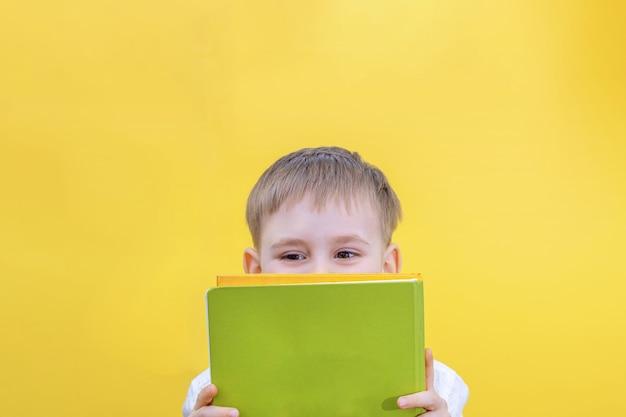 Um lindo menino loiro olha astutamente por trás de um livro o conceito da escola de volta à escola
