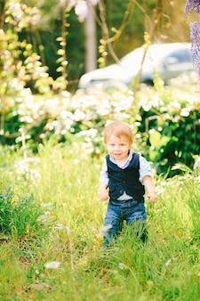 Um lindo menino ruivo está de pé em uma grama verde no parque em um dia ensolarado