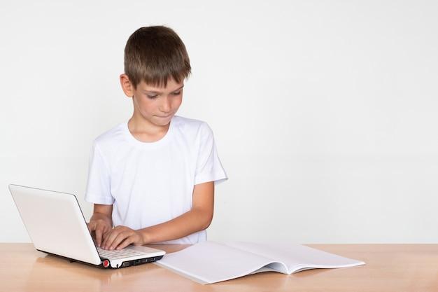 Um lindo menino se senta à mesa, imprime em um laptop, olha para um caderno ou livro sobre um fundo branco