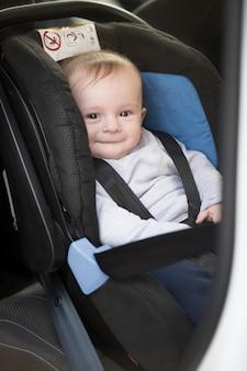Um lindo menino sorridente sentado na cadeirinha do carro