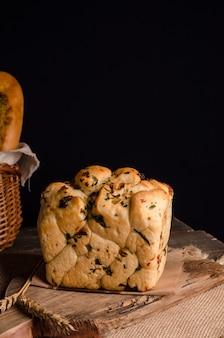 Um lindo pedaço de pão branco com uma parte superior encaracolada com espaço de cópia em um fundo de madeira