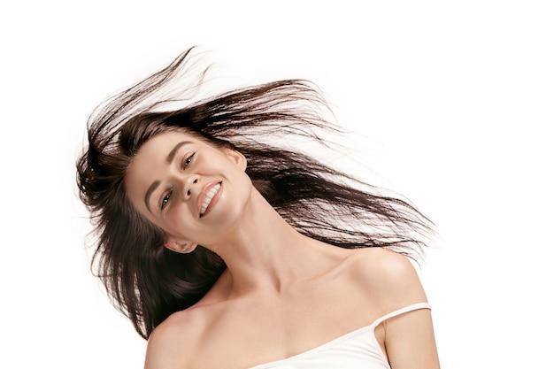 Um lindo rosto feminino. pele perfeita e limpa de jovem caucasiana em fundo branco do estúdio.