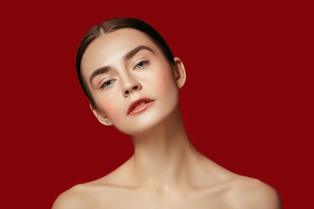 Um lindo rosto feminino. pele perfeita e limpa de jovem caucasiana em fundo vermelho studio.