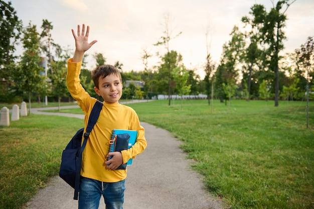 Um lindo simpático e charmoso colegial de 9 anos, no parque, com uma mochila no ombro e cadernos nas mãos, acena com a mão, olha em volta e sorri docemente com um sorriso dentuço.