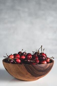 Um lindo vaso de madeira cheio de frutas vermelhas. prato com cerejas. vegan, eco, produto agrícola, comida orgânica