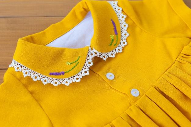 Um lindo vestido infantil feito de algodão natural com bordado de flores roxas na gola. renda na gola. roupas infantis. um vestido para uma menina.