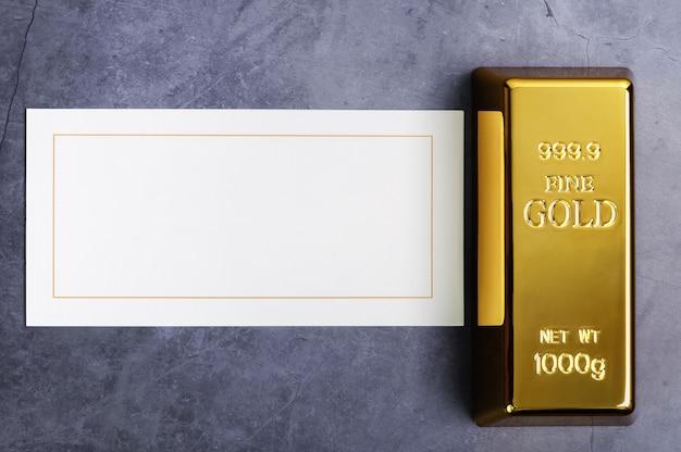 Um lingote de lingote de metal ouro de puro brilhante sobre um fundo cinza texturizado.