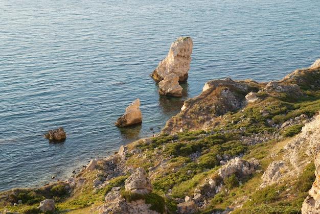 Um litoral com muitas rochas grandes.